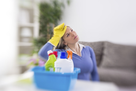 domestic production: Female worker from cleaning service is tired of cleaning house Stock Photo