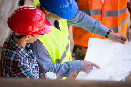 site manager  looking blueprint with architects Stock Photo