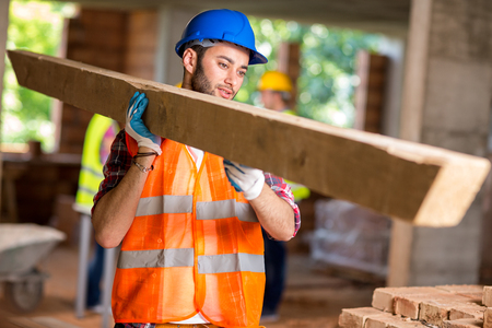bring: Young worker bring construction timber at work