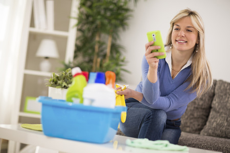 short gloves: Attractive blond woman look at mobile phone during break from cleaning house Stock Photo