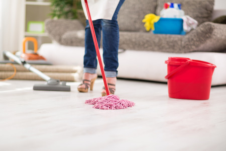 Close up of mop, worthy housewife with mop cleans floor in room