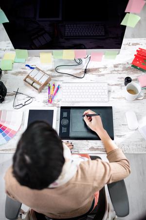 Diseñador de la mujer escribiendo en la mesa de la pluma en la oficina de vista superior Foto de archivo - 54016446