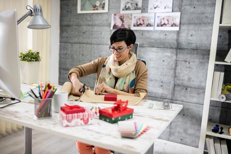 prepare: smiling designer prepare gift for client