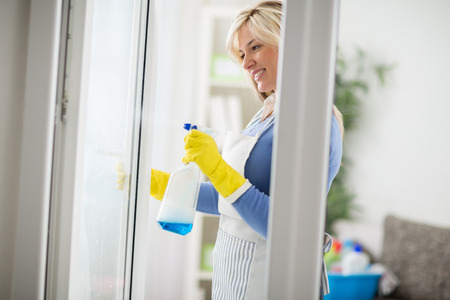 spring tide: Young housemaid use liquid with spray for windows
