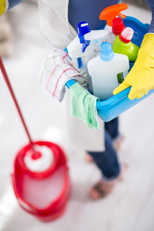 Housewife wears bucket with chemicals, cloths and mop for cleaning house