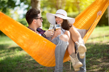 lassie: Lovely lassie with boyfriend toast with glasses of beer in hammock in forest