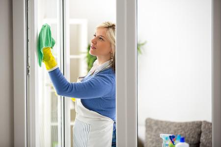 diligente: mujer joven diligente limpia la ventana en el apartamento Foto de archivo