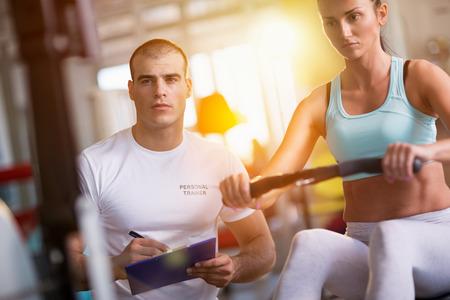 hilera: deporte, fitness, estilo de vida, y las personas concepto - mujer feliz y animador de trabajo a la máquina para hacer ejercicios en el gimnasio Foto de archivo