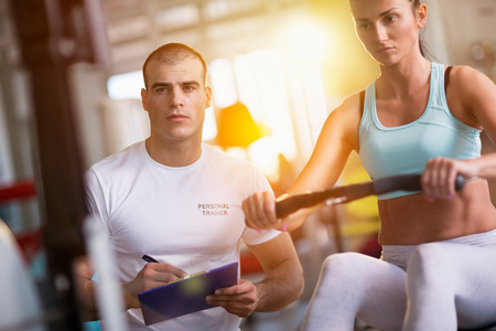 in a row: sport, fitness, lifestyle, and people concept - happy woman and trainer working out on exercise machine in gym Stock Photo