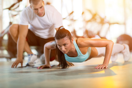supervisi�n: Young woman doing push ups under supervision of a trainer at gym