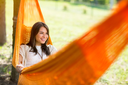 hammock: Young cheerful female lying down in orange hammock and resting in nature