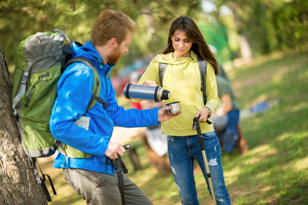 thermos: Young female hikers pours water from thermos to his male friend in nature