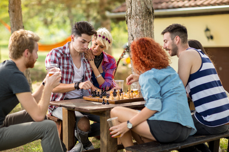 Youngsters thinks while playing chess in nature