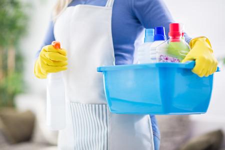 asimiento de la mujer de plástico palangana llena de productos para la limpieza de la casa