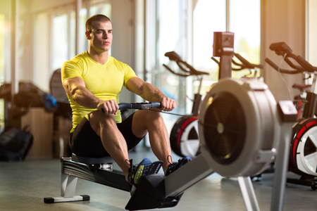Sporty man exercising in gym on row machine