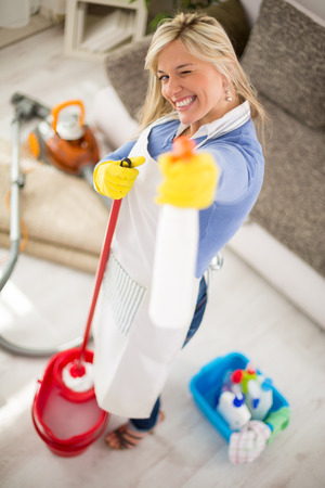 tidying up: Cheerful housemaid with products for cleaning house in hands make joke Stock Photo