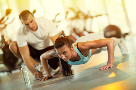 Young man motivating gym woman  during push ups exercise