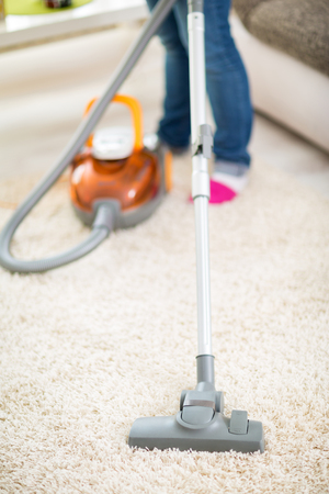 professionally: Close up of vacuuming carpet in apartment with vacuum cleaner
