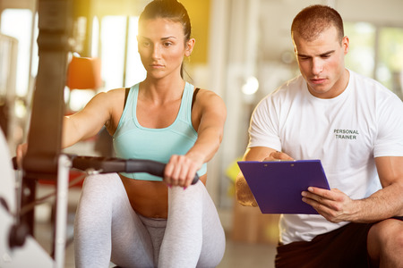 Trainer taking notes of attractive woman on exercise machine in gym