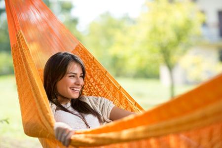 hamaca: muchacha sonriente joven goza en la hamaca en maderas Foto de archivo