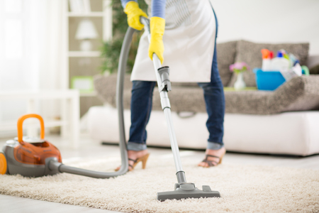 Woman from cleaning service cleans carpet with vacuum cleaner