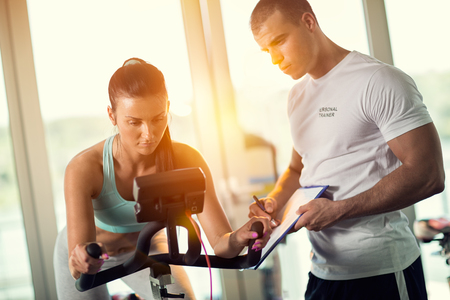 Personal trainers in the gym giving instruction and help to attractive young women on JTF bicycles Stock Photo
