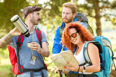 thermos: Tattooed man poured coffee from thermos while female look at map in woods