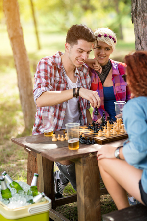 move in: Guy pulls a move in chess game on picnic in nature