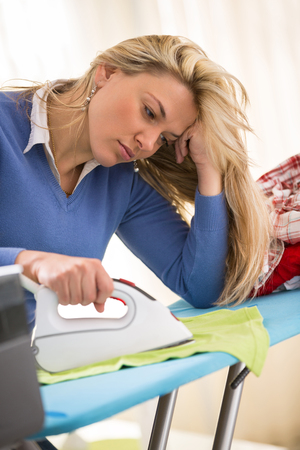 tiring: Sometimes ironing is tiring and boring job for young hostess