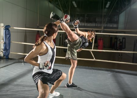 patada: Tiro energía femenina boxeador que practica en el ring de boxeo