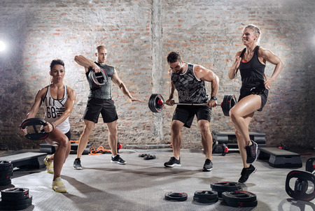 group of muscular sporty people practicing with weights Stock Photo