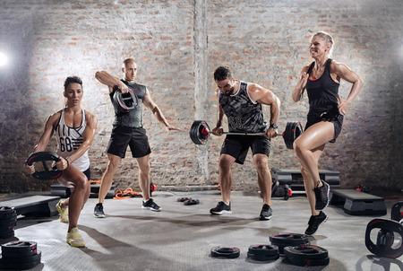 pesas: grupo de los deportistas que practican con los pesos musculares Foto de archivo