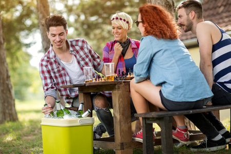 refreshes: Cold beer refreshes youngsters while playing chess in woods