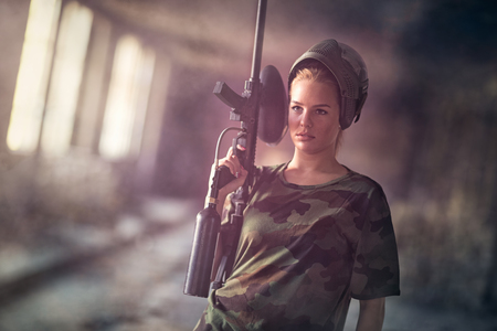 paintball: Attractive young woman with marker gun, paintball sport and leisure