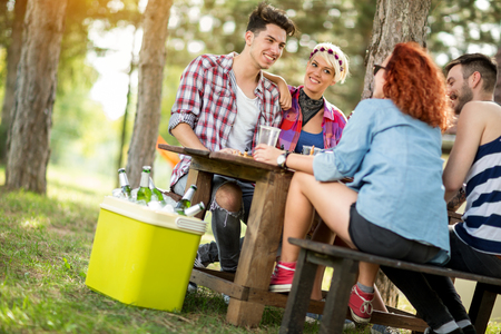 picnic table: Girls and guys sits on bench at wooden table in forest, drink beer and make jokes Stock Photo