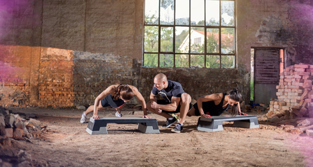 male athlete: Two female with trainer doing push-ups in hangar