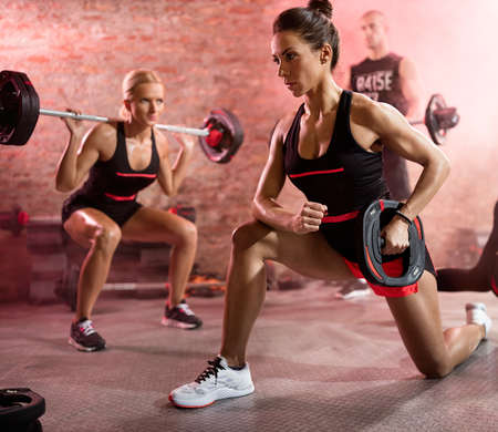 muscular woman training with weights, body pump