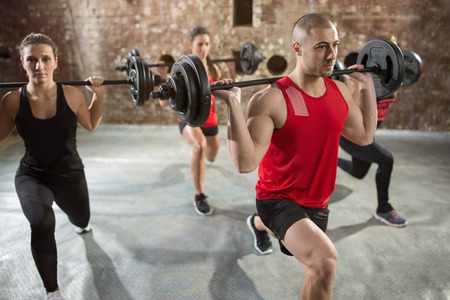 body pump: group people well trained bodybuilder with dumbbells