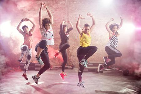 Grupo de mujeres jóvenes aptos que bailan y que ejercen