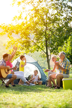 happy family enjoying on summer day on camping