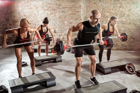 Group of fit people doing exercise with weights, total body workout