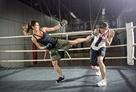 patada: Tiro femenina boxeador que practica en el ring de boxeo