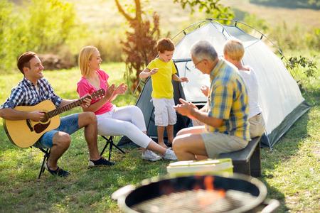 ni�o cantando: ni�o que canta con la sonrisa de la familia en acampar
