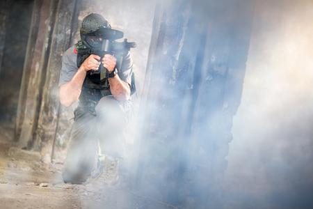 paintball: Young paintball player shooting thought smoke