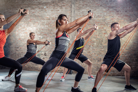 group exercising with elastic band, training class