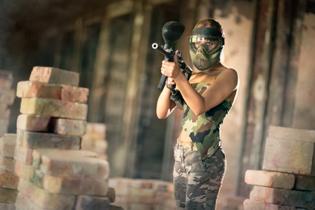 paintball: woman in camouflage  uniform with mask, paintball game in runs