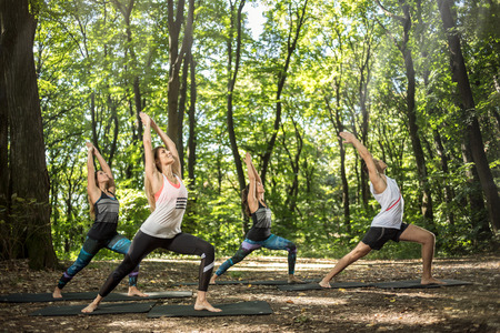 practitioners: Young yoga and balance practitioners training in shiny forest
