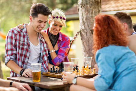 opponent: Guy play chess with opponent in game at nature and girl gives him support Stock Photo