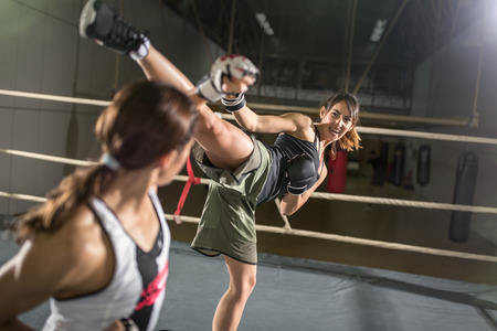 the attack: energy women practicing body combat attack in boxing ring