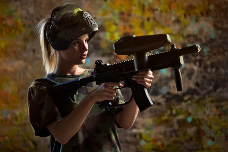 aiming: Girl paintballer with marker gun and mask
